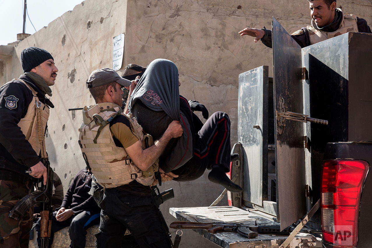 Iraqi security officers place a suspected Islamic State group member into the back of a waiting pickup truck, in east Mosul on Feb. 21, 2017. (AP Photo/John Beck)
