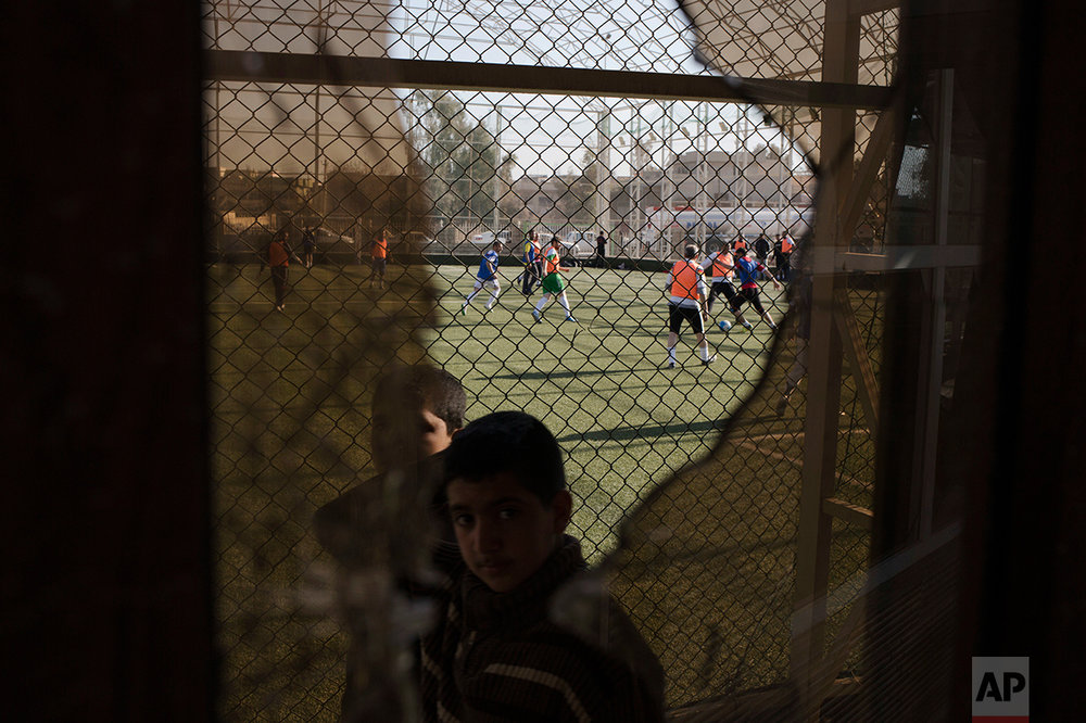 A child passes a broken window, damaged by fighting between Iraqi forces and Islamic State militants, while Mosul residents play soccer in the background on Feb. 7, 2017. After months of fighting, Mosul residents can finally practice their favorite game again at the soccer field in the eastern part of the city—and this time without the changes imposed by Islamic State militants. (AP Photo/Bram Janssen)
