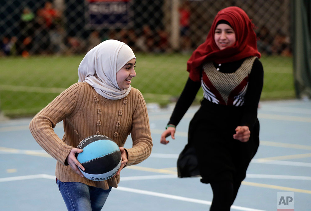 Syrian refugee girls play a basketball game at a private sports club, southern Beirut, Lebanon on Sunday, Feb. 19, 2017. (AP Photo/Hussein Malla)