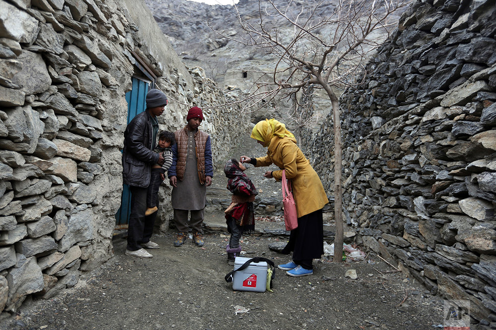 An Afghan health worker vaccinates a child as relatives watch during a campaign to eliminate polio on the outskirts of Kabul, Afghanistan, Tuesday, Feb. 28, 2017. (AP Photo/Rahmat Gul)