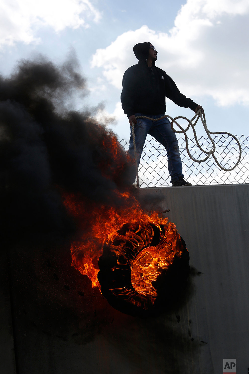 Palestinian protesters climb over the separation barrier with Israel during a demonstration marking the 12th anniversary of their campaign against Israel's separation barrier in the West Bank village of Bilin near Ramallah, Friday, Feb. 17, 2017. (AP Photo/Majdi Mohammed)