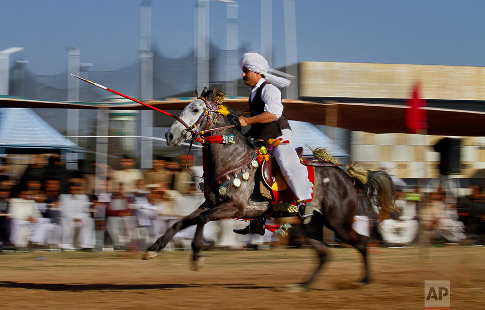 A Pakistani rider races to target a wooden peg during a tent pegging competition organized by the Pakistan Sports Board, in Islamabad, Pakistan, Sunday, Feb. 26, 2017. In tent pegging, a horseman gallops and uses a sword or a lance to pierce, pick up, and carry away a wooden peg. (AP Photo/Anjum Naveed)