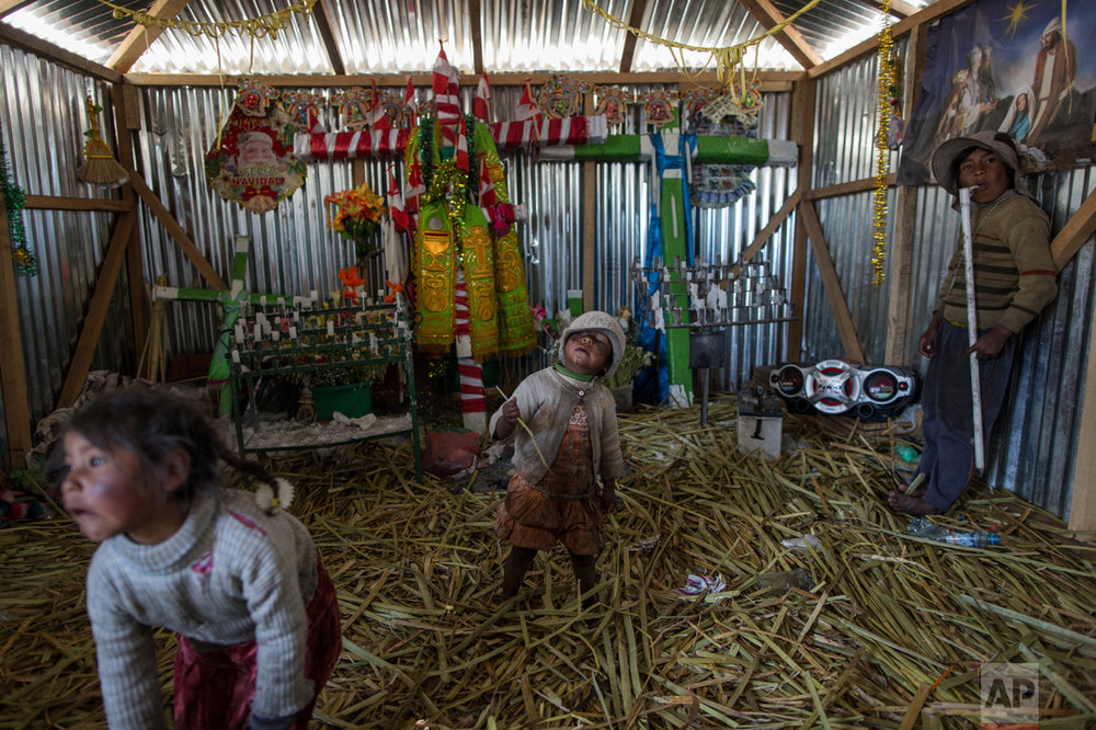 In this Feb. 2, 2017 photo, children play inside a church in Kapi Cruz Grande, a community on the shores of Lake Titicaca in the Puno region of Peru. Many living on the 4,000-meter (13,100-feet) high plain surrounding the lake contaminated with toxic levels of lead and mercury feel government leaders have neglected them. (AP Photo/Rodrigo Abd)