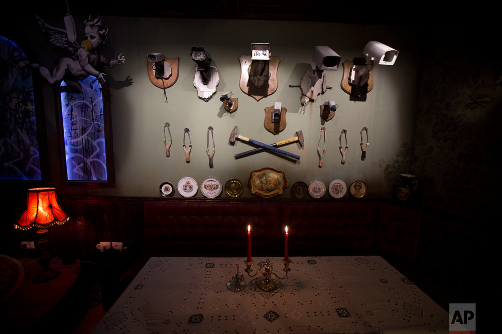 "A wall decorated with security cameras and slingshots is seen in the bar area of the ""The Walled Off Hotel"" and the Israeli security barrier in the West Bank city of Bethlehem, Friday, March 3, 2017. The owner of a guest house packed with the elusive artist Banksy's work has opened the doors of his West Bank establishments to media, showcasing its unique ""worst view in the world."" The nine-room hotel named ""The Walled Off Hotel"" will officially open on March 11. (AP Photo/Dusan Vranic)"