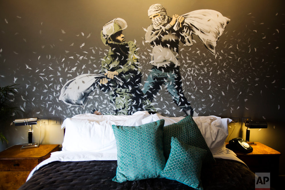 "A Banksy wall painting showing Israeli border policeman and Palestinian in a pillow fight is seen in one of the rooms of the ""The Walled Off Hotel"" in the West Bank city of Bethlehem, Friday, March 3, 2017. The owner of a guest house packed with the elusive artist Banksy's work has opened the doors of his West Bank establishments to media, showcasing its unique ""worst view in the world."" The nine-room hotel named ""The Walled Off Hotel"" will officially open on March 11. (AP Photo/Dusan Vranic)"