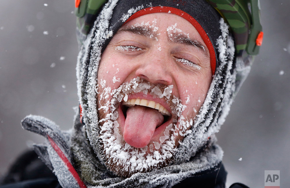 Cyclist David Cassidy of Bangor, Maine, enjoys the moment after crossing the finish line in an 18-mile bike race at the Fat Tire Festival at the Sugarloaf ski resort, Saturday, Feb 11, 2017, in Carrabassett Valley, Maine. Riders had to endure heavy snowfall and 2 degree F temperatures as parts of New England get hit with another winter storm. (AP Photo/Robert F. Bukaty)
