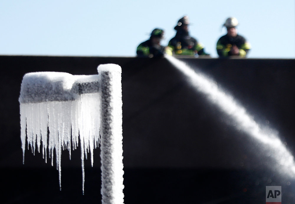 Icicles are formed on a street lamp as firefighters douse over an area at a large apartment complex, Saturday, Feb. 4, 2017, in Maplewood, N.J. Authorities said the fast-moving fire has destroyed most of the luxury apartment complex that was about to open to residents. Town officials said 235 units were planned for the complex overall, and roughly 30 of them were due to be ready for occupancy in about six weeks. AvalonBay, which owns the complex, faced a similar situation two years ago when a 240-unit apartment complex it operated in Edgewater was gutted by a massive blaze. (AP Photo/Julio Cortez)