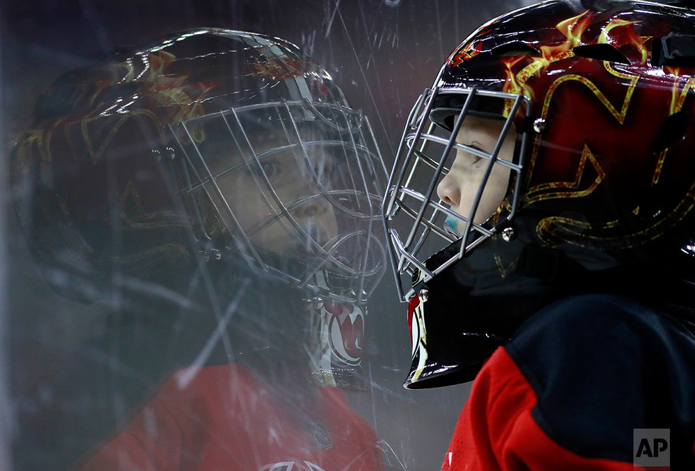 Santiago Lopes, 3, of Newark, N.J., wears a goalie helmet as he watches action during the first period of an NHL hockey game between the New Jersey Devils and the Ottawa Senators, Tuesday, Feb. 21, 2017, in Newark, N.J. (AP Photo/Julio Cortez)