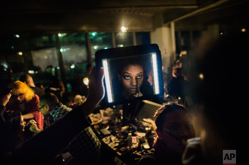 A make artist work on a model as her assistant light the model's face during the Brandon Maxwell show at the Fashion Week, Tuesday, Feb. 14, 2017, in New York. (AP Photo/Andres Kudacki)