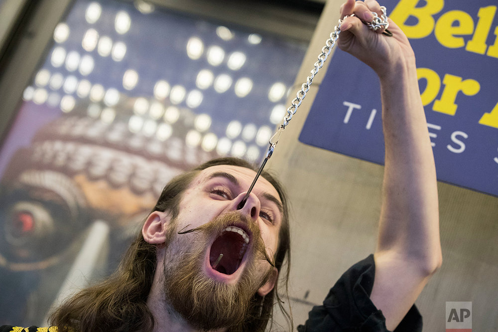 Kyle Mertz, of Emmaus, Pa., performs with a giant fishing hook during the 10th annual World Sword Swallower's Day at the Ripley's Believe it or Not!, Saturday, Feb. 25, 2017, in New York's Times Square. (AP Photo/Mary Altaffer)