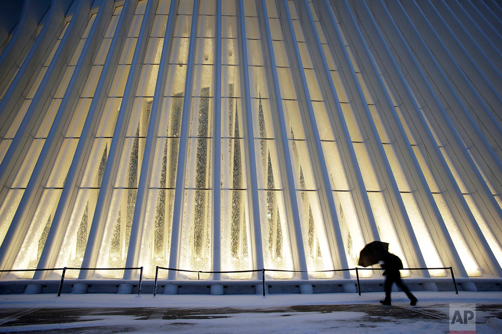 A man makes his way through wind and snow past the Oculus of the World Trade Center Transportation Hub, Thursday, Feb. 9, 2017, in New York. A powerful, fast-moving storm swept through the northeastern U.S. Thursday, making for a slippery morning commute and leaving some residents bracing for blizzard conditions. (AP Photo/Mark Lennihan)