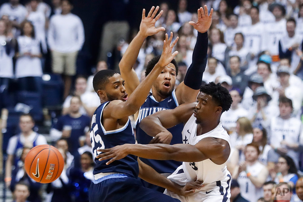 Xavier's Quentin Goodin, right, passes against Villanova's Mikal Bridges (25) and Jalen Brunson, center, in the first half of an NCAA college basketball game, Saturday, Feb. 11, 2017, in Cincinnati. (AP Photo/John Minchillo)