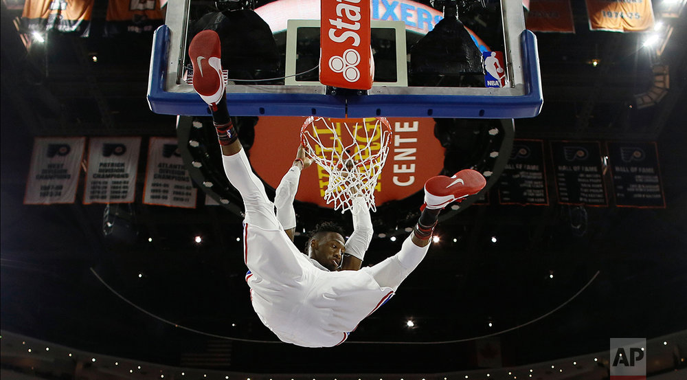 Philadelphia 76ers' Robert Covington hangs on the rim after a dunk during the second half of an NBA basketball game against the San Antonio Spurs, Wednesday, Feb. 8, 2017, in Philadelphia. San Antonio won 111-103. (AP Photo/Matt Slocum)