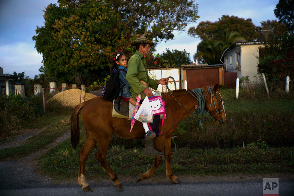 In this Feb. 28, 2017 photo, a tobacco worker takes his daughter to school on horseback in Cuba's western province Pinar del Rio. Despite the flood of visitors since Cuba and the U.S. reestablished relations, some aspects of life in the provinces have changed little. (AP Photo/Ramon Espinosa)