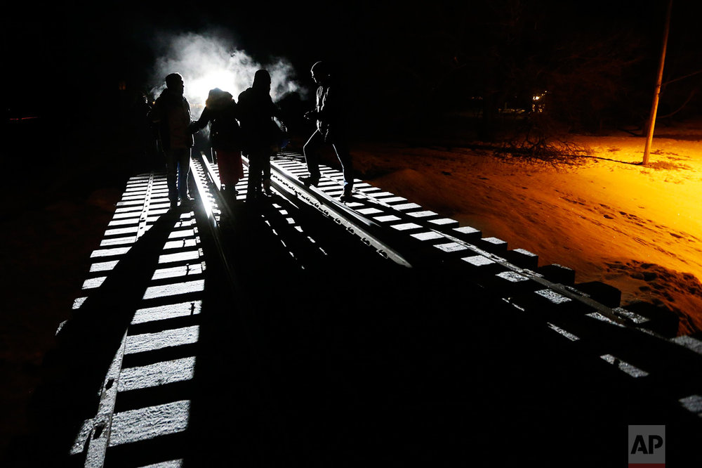 Migrants from Somalia cross into Canada from the United States by walking down a train track early Sunday, Feb. 26, 2017, into the town of Emerson, Manitoba, where they will seek asylum at the Canada Border Services Agency. (John Woods/The Canadian Press via AP)