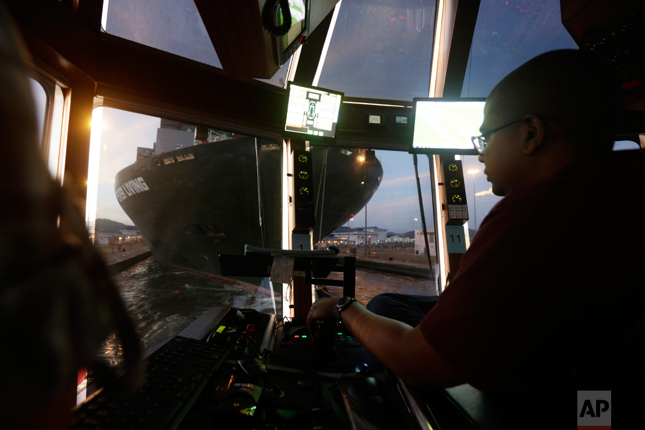 In this Jan. 18, 2017 photo, tugboat Captain Antonio Wray guides the Ever Living, a Neo-Panamax cargo ship, through the Cocoli locks that are part of the new Panama Canal expansion project in Cocoli, Panama. Before the canal opened in late June 2016, tugboat pilots expressed concern about what they said was insufficient training for new maneuvers that are now required. (AP Photo/Arnulfo Franco)