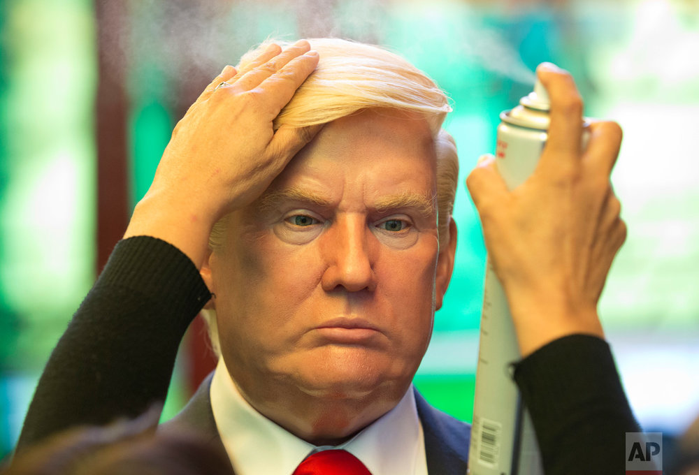 Museum worker Monica Alcantara adjusts the hair on a wax replica of U.S. President Donald Trump at the Wax Museum in Mexico City, Wednesday, Feb. 1, 2017. The wax figure of Trump went on display the day of his inauguration, Jan. 20, and currently stands next to Mexican President Enrique Pena Nieto at the museum's entrance. (AP Photo/Rebecca Blackwell)