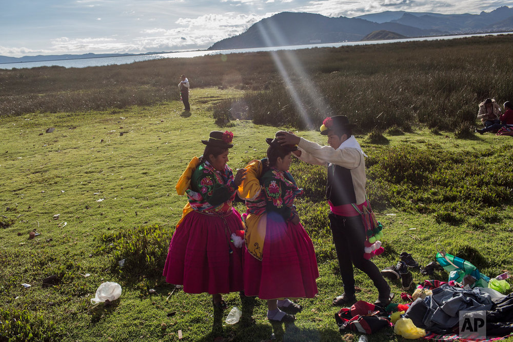 In this Jan. 29, 2017 photo, dancers get ready near Lake Titicaca prior to their performance at Virgin of Candelaria celebrations in Puno, Peru. The festivities start this week. (AP Photo/Rodrigo Abd)