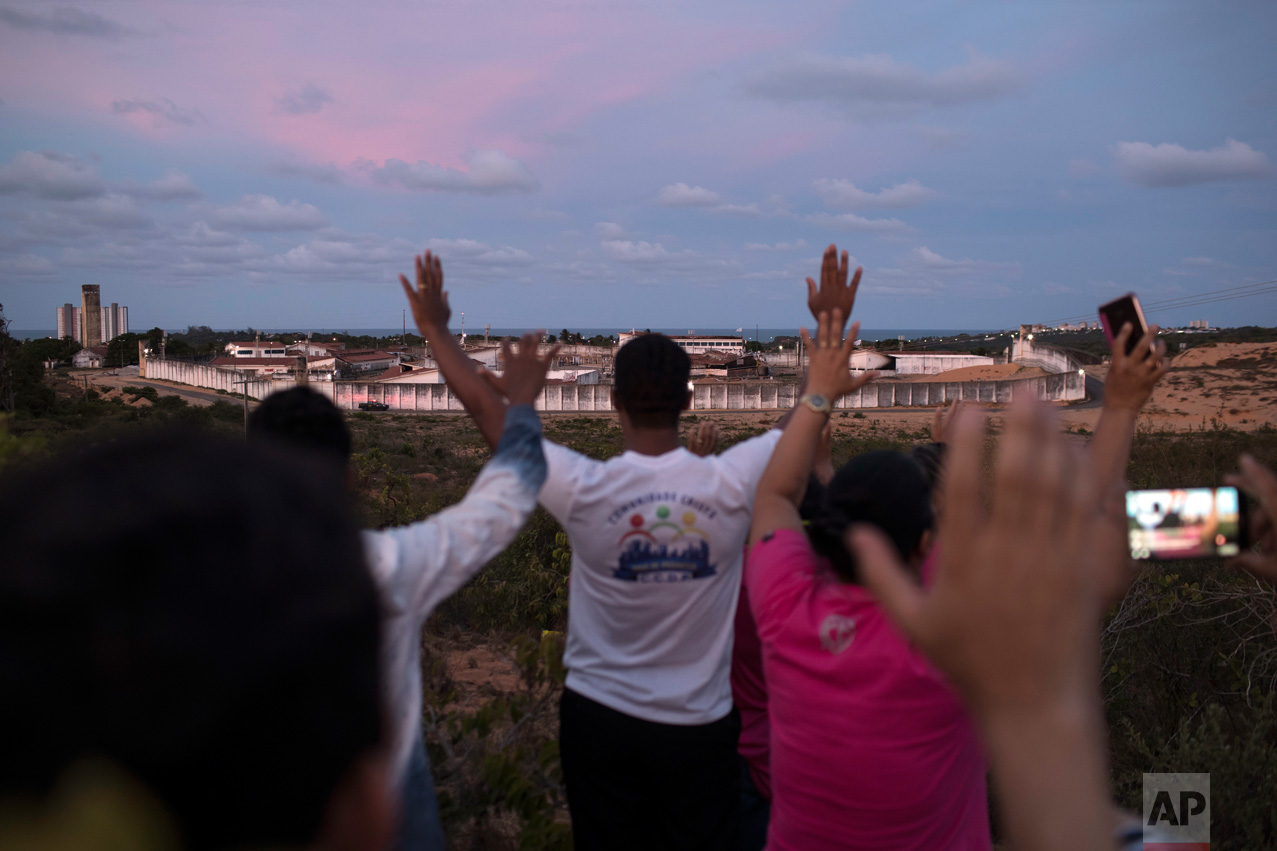 In this Jan. 20, 2017 photo, people pray for peace as they face Alcacuz prison in Nisia Floresta, near Natal, Brazil. Authorities acknowledge that Alcacuz is beyond saving. Rio Grande do Norte state Gov. Robinson Faria has announced it will close, though only after three new prisons are ready. In the meantime, an emergency force of corrections agents has been sent in to establish order and repair the damaged facility. (AP Photo/Felipe Dana)