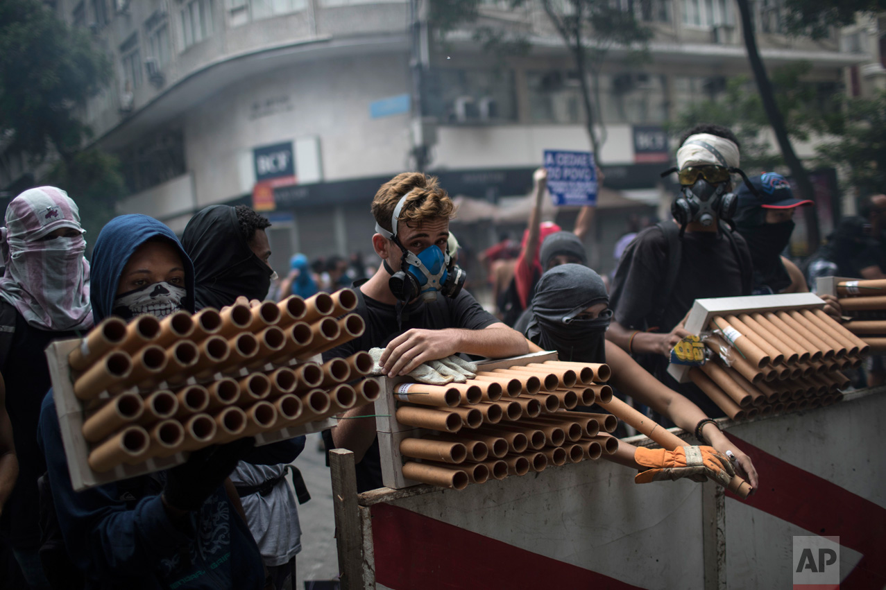 Demonstrators holding fireworks as weapons stand behind a barricade during clashes with police as they protest the state government in Rio de Janeiro, Brazil, Thursday, Feb. 9, 2017. The protesters are denouncing a proposal to privatize the state's water and sewage company. (AP Photo/Felipe Dana)