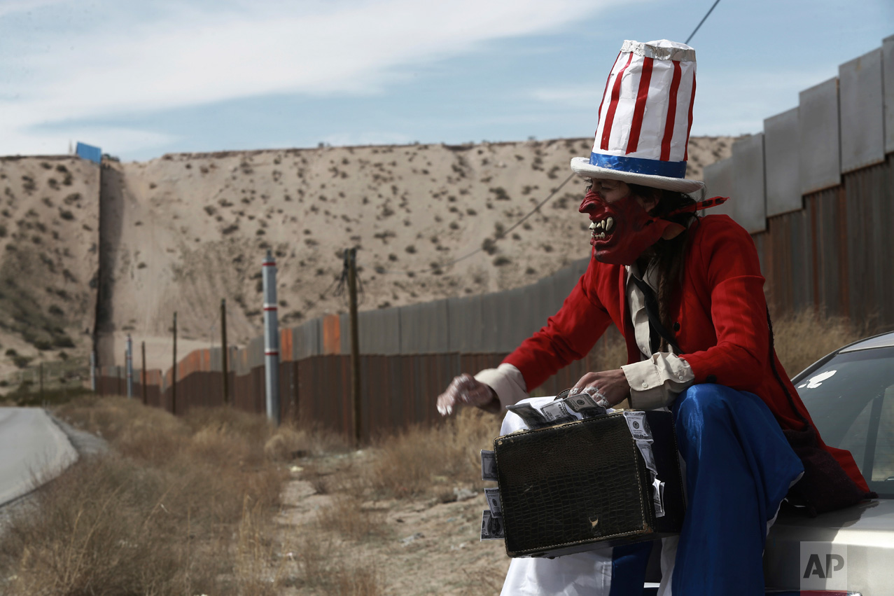 A protester dressed as a diabolical version of Uncle Sam holds a suitcase full of money at the U.S. border fence in Ciudad Juarez, Mexico, Sunday, Feb. 26, 2017. A group of about 30 protestors gathered to paint slogans on the border wall and stage a performance mocking the relationship between Presidents Donald Trump and Enrique Pena Nieto. (AP Photo/Christian Torres)