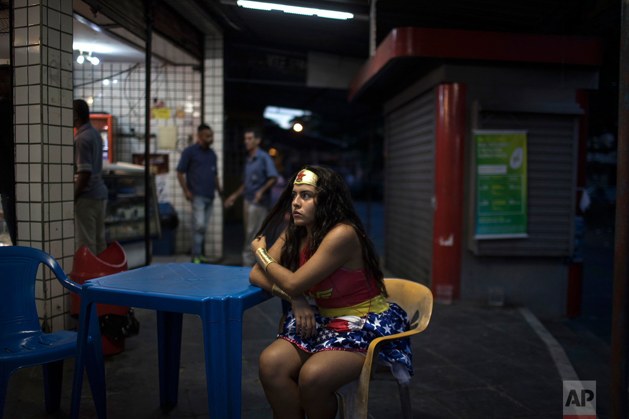"A reveler wearing a wonder woman costume sits at a bar during carnival festivities at the Cidade de Deus, or ""City of God"" slum in Rio de Janeiro, Brazil, Monday, Feb. 27, 2017. (AP Photo/Felipe Dana)"