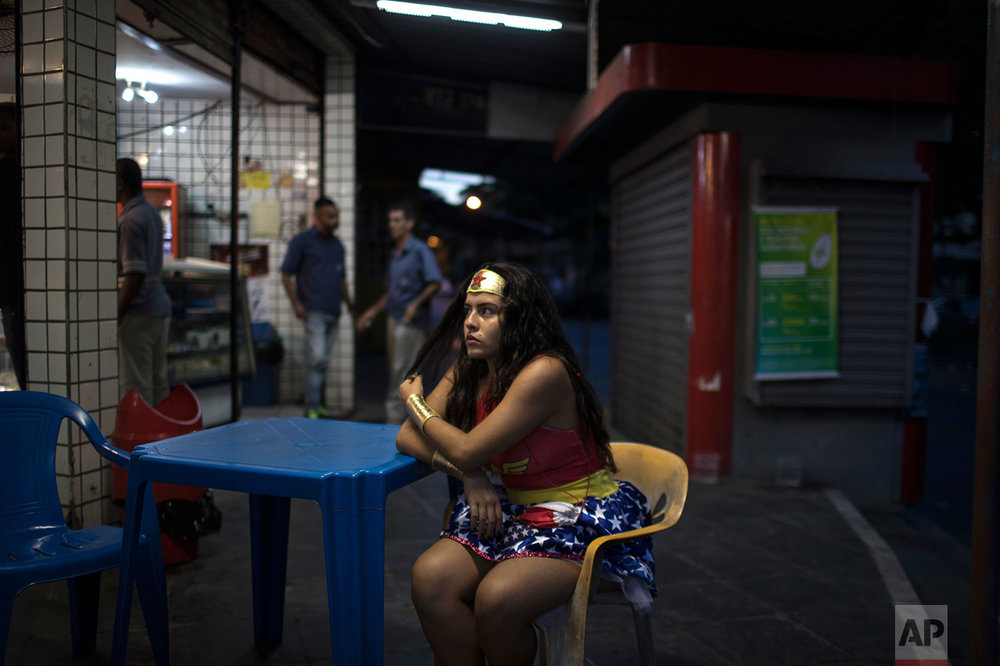 "A reveler wearing a wonder woman costume sits at a bar during carnival festivities at the Cidade de Deus, or ""City of God"" slum in Rio de Janeiro, Brazil, Monday, Feb. 27, 2017. (AP Photo/Felipe Dana)"