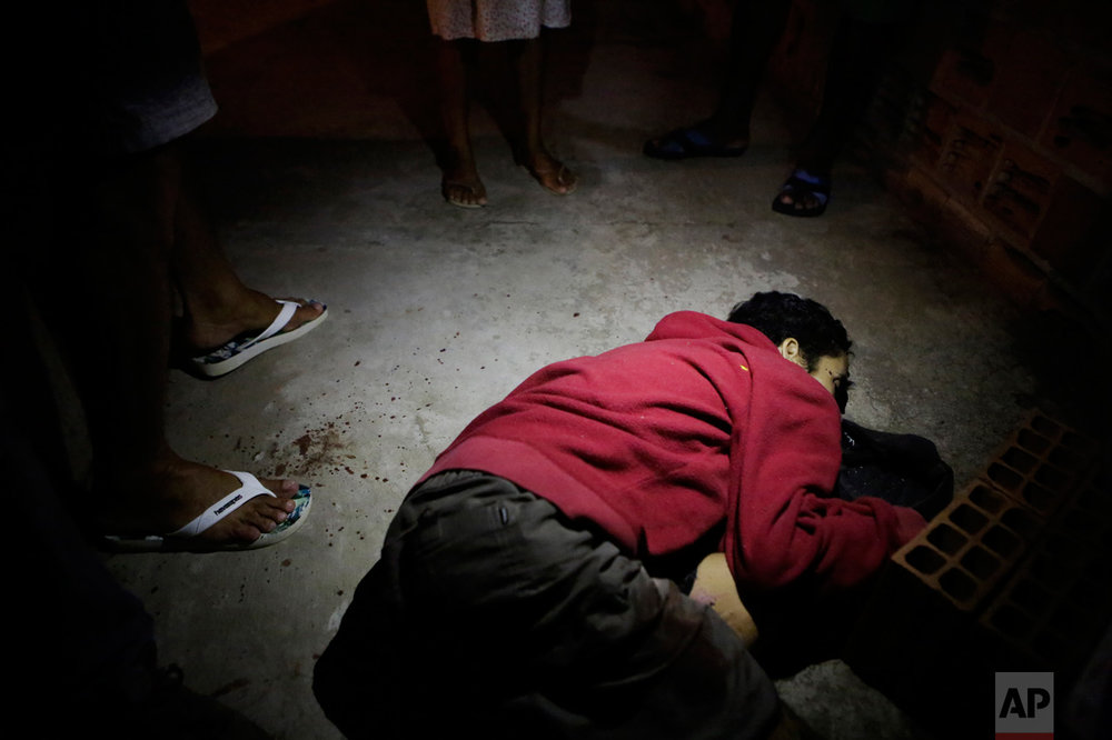 In this Thursday, Feb 9, 2017 photo, Nelson Eduardo Conclaves lies in a pool of blood as a neighbor stands over him in Vitoria, Espirito Santo state, Brazil. According to his mother Erlita Pereira Goncalves, her 30-year-old son was shot dead by attackers who broke into their home and killed him in front of her. (AP Photo/Diego Herculano)