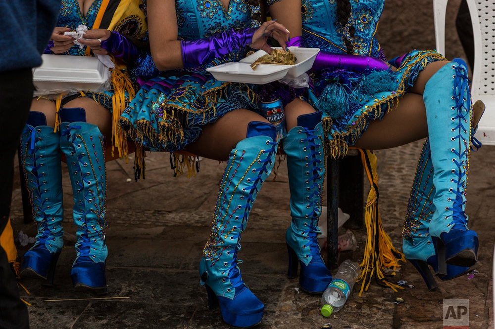 Dancers eat lunch during a break from performing at the Virgin of Candelaria celebrations in Puno, Peru, Sunday, Feb. 5, 2017. (AP Photo/Rodrigo Abd)