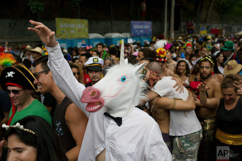 "A reveler wearing a unicorn mask enjoys the ""Ceu na Terra"" or Heaven on Earth street party in Rio de Janeiro, Brazil, Saturday, Feb. 25, 2017. Merrymakers take to the streets in hundreds of open-air ""bloco"" parties during Rio's over-the-top Carnival, the highlight of the year for many. (AP Photo/Leo Correa)"