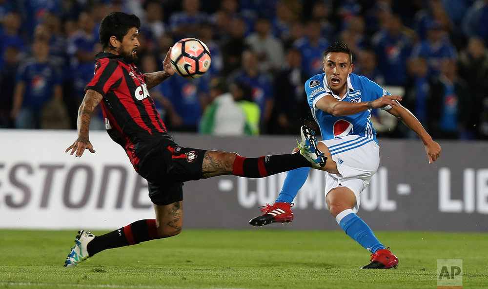 Lucho Gonzalez of Brazil's Atletico Paranaense, left, tries to block a kick by Henry Rojas of Colombia's Millonarios, during a Copa Libertadores soccer match in Bogota, Colombia, Wednesday, Feb. 8, 2017. (AP Photo/Fernando Vergara)