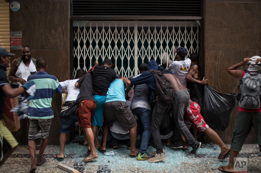 People break into a store during clashes with riot police at a protest against the state government in Rio de Janeiro, Brazil, Thursday, Feb. 9, 2017. The protesters are denouncing a proposal to privatize the state's water and sewage company. (AP Photo/Felipe Dana)