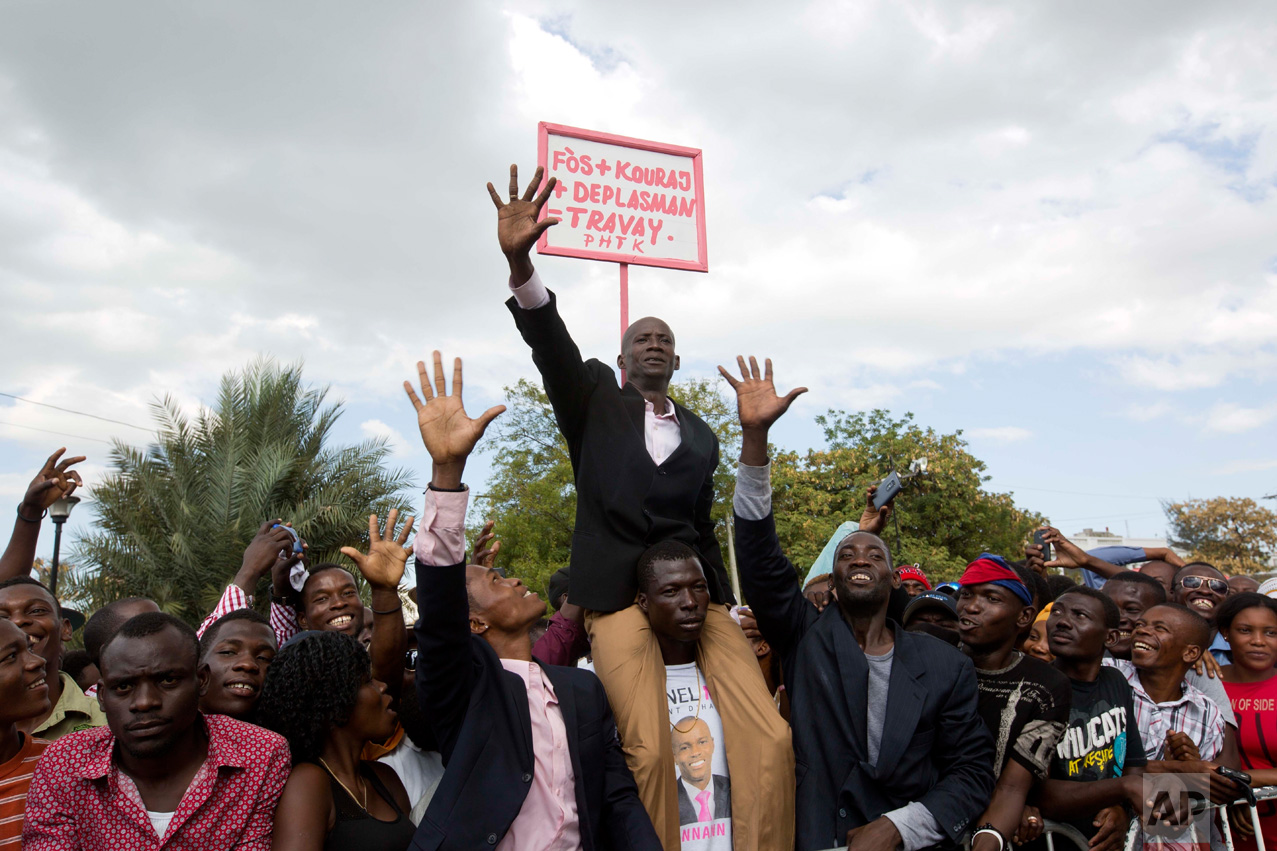 "A supporter of Haiti's President Jovenel Moise impersonates the new president, with a sign behind him that reads in Creole ""Energy plus encouragement plus movement plus work"" during Moise's inauguration in Port-au-Prince, Haiti, Tuesday, Feb. 7, 2017. Moise was sworn-in as president for the next five years after a bruising two-year election cycle, inheriting a struggling economy and a deeply divided society. (AP Photo/Dieu Nalio Chery)"