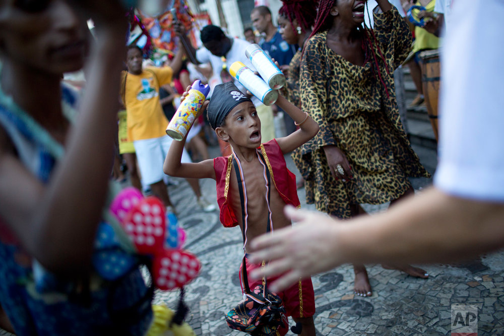 "A youth sells foam cans to revelers during the ""Get out Temer"" carnival street party in Rio de Janeiro, Brazil, Friday, Feb. 24, 2017. Merrymakers took to the streets to protest Brazil's President Michel Temer. (AP Photo/Silvia Izquierdo)"