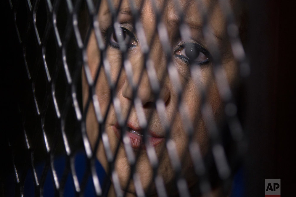 Supreme Court Justice Blanca Stalling looks out from a cell at a court in Guatemala City, Wednesday, Feb. 8, 2017. Prosecutors in Guatemala say Stalling has been arrested on a charge of influence peddling for trying to help her son in a corruption case. (AP Photo/Luis Soto)