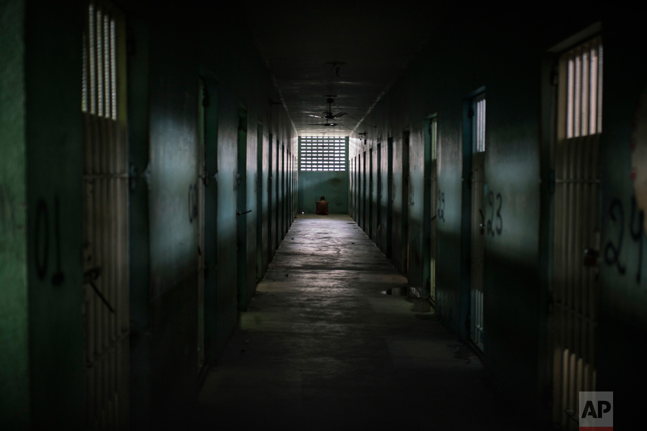 In this Feb. 2, 2017 photo, an inmate sits facing the wall at the end of a corridor between cells at the Monte Cristo agricultural penitentiary in Boa Vista, Brazil. Some prisoners serving time for lesser crimes were forced to participate in gang-driven slaughters that left at least 130 inmates dead in January at this jail, and one other. (AP Photo/Felipe Dana)