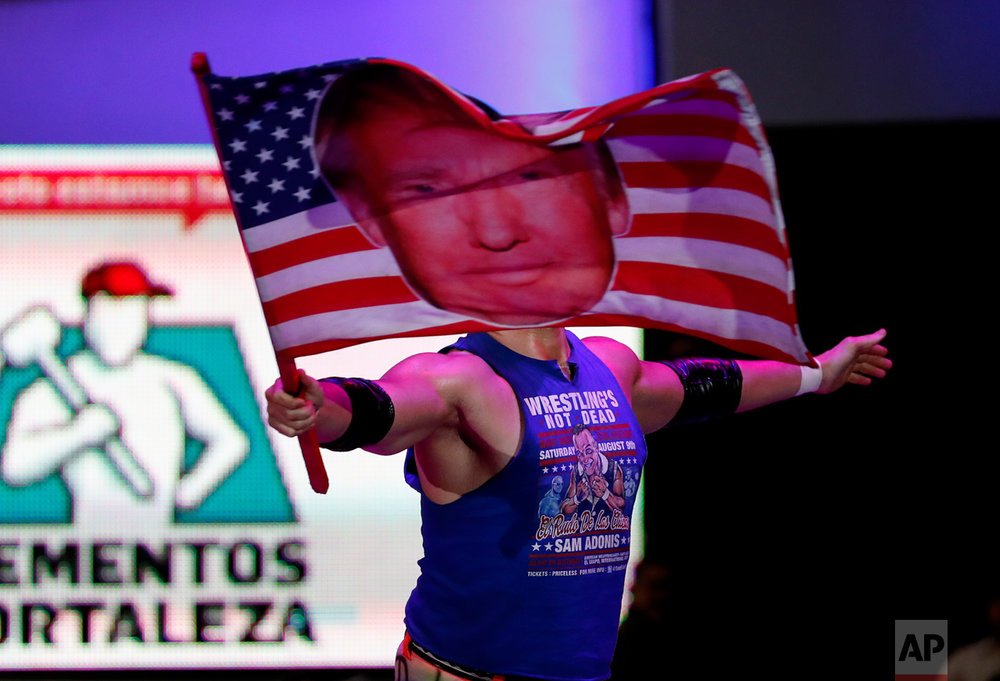 American pro wrestler Sam Polinsky aka Sam Adonis takes the ring at Arena Mexico waving an American flag emblazoned with a photo of U.S. President Donald Trump, in Mexico City, Sunday, Feb. 12, 2017. He's the guy Mexicans love to hate: The wrestler has become a sensation in Mexico City by adopting the ring persona of a flamboyant Trump supporter. (AP Photo/Eduardo Verdugo)