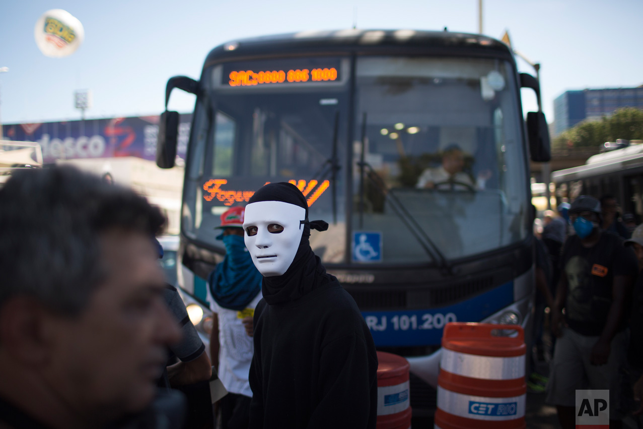 A masked demonstrator stands in front a bus as he blocks a street next to the Sambodrome during a protest against the state government in Rio de Janeiro, Brazil, Monday, Feb. 20, 2017. The protesters are denouncing a proposal to privatize the state's water and sewage company. (AP Photo/Leo Correa)