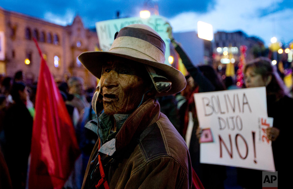 "A Quechua Indian watches a protest march against Bolivia's President Evo Morales, while a woman holds a sign with a message that reads in Spanish; ""Bolivia said no!"" regarding a referendum ruling out his run for a fourth term, in La Paz, Bolivia, Tuesday, Feb. 21, 2017. (AP Photo/Juan Karita)"
