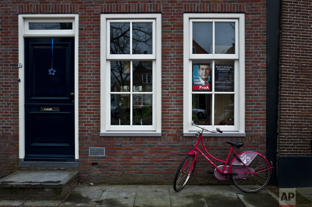 In this Friday, March 3, 2017 photo, an election poster showing Lodewijk Asscher, from the Labour Party, PvdA, is displayed on the window of a home in Edam, Netherlands. March 15 marks the general election in the Netherlands. (AP Photo/Muhammed Muheisen)
