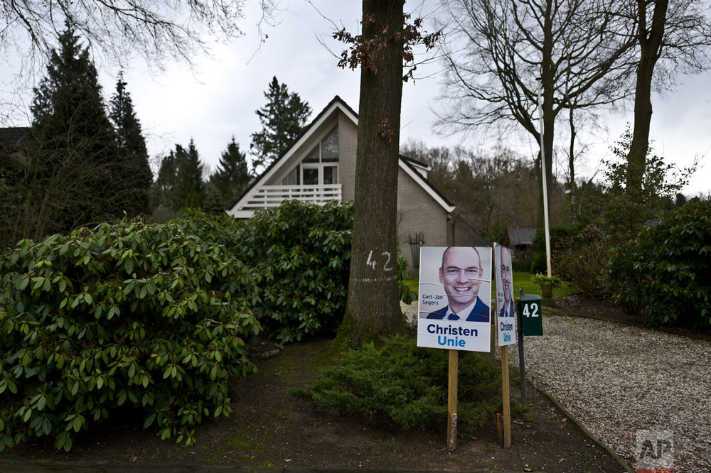 In this Saturday, March 4, 2017 photo, an election poster showing Gert-Jan Segers, from the Christian Union party, CU, is displayed by the entrance of a home in Putten, Netherlands. March 15 marks the general election in the Netherlands. (AP Photo/Muhammed Muheisen)
