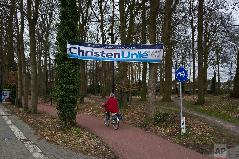 "In this Saturday, March 4, 2017 photo, an election banner supporting the Christian Union, CU, is hung on trees in a cycling lane in Putten, Netherlands. March 15 marks the general election in the Netherlands. Banner reads in Dutch ""Respect, Care, Faithfully, Hope, Christian Union, give faith a voice"". (AP Photo/Muhammed Muheisen)"