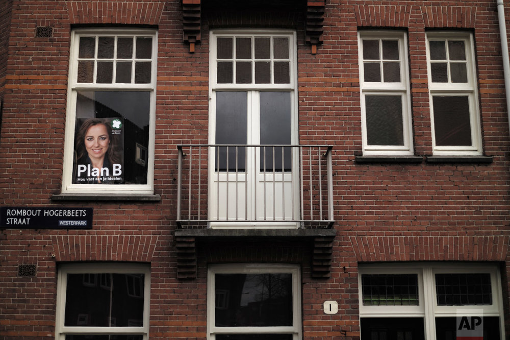 In this Wednesday, March 1, 2017 photo, an election poster showing Marianne Thieme, from the Party for the Animals, PvdD, is displayed on the window of a house in Amsterdam, Netherlands. March 15 marks the general election in the Netherlands. (AP Photo/Muhammed Muheisen)