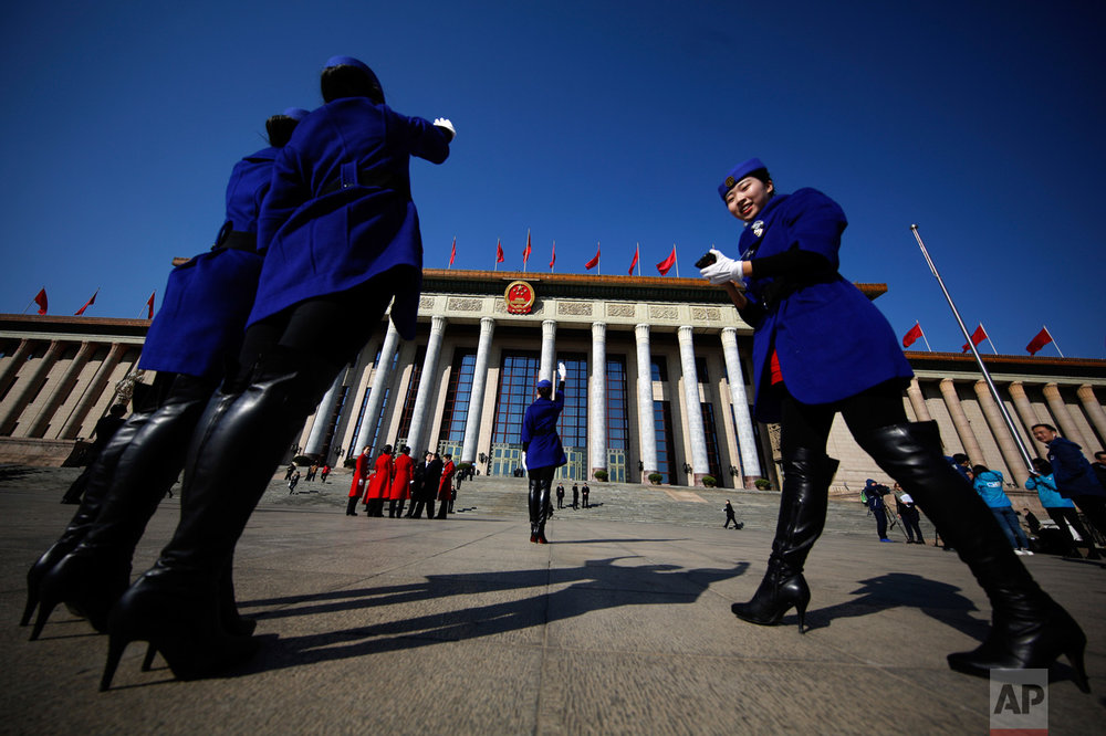 In this Sunday, March 5, 2017, photo, hospitality staff take souvenir photos in front of the Great Hall of the People where the National People's Congress is held in Beijing. (AP Photo/Andy Wong)
