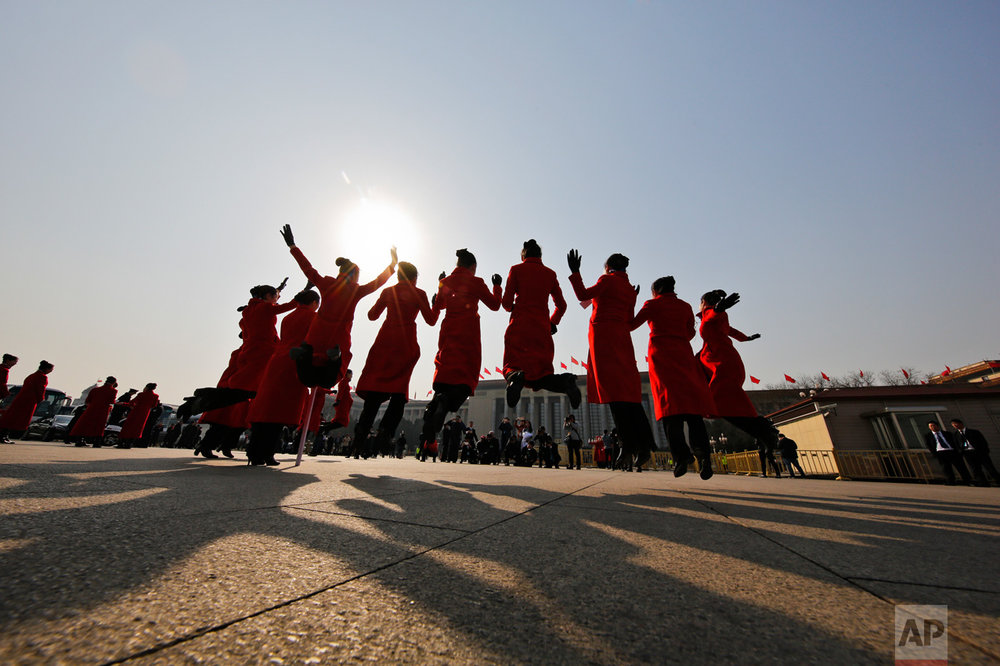 In this Friday, March 3, 2017 photo, hospitality staff jump as they pose for photographs on Tiananmen Square during the Chinese People's Political Consultative Conference (CPPCC) held at the Great Hall of the People in Beijing. (AP Photo/Andy Wong)