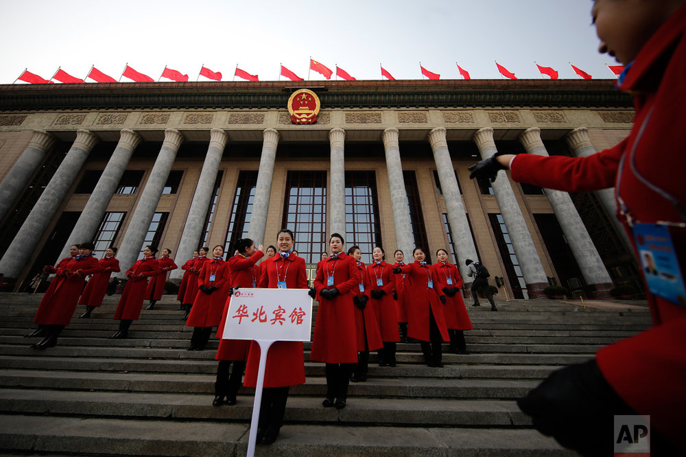 In this Friday, March 3, 2017 photo, a hospitality staffer directs her colleagues posing for photographs outside the Great Hall of the People during the Chinese People's Political Consultative Conference (CPPCC) in Beijing. (AP Photo/Andy Wong)