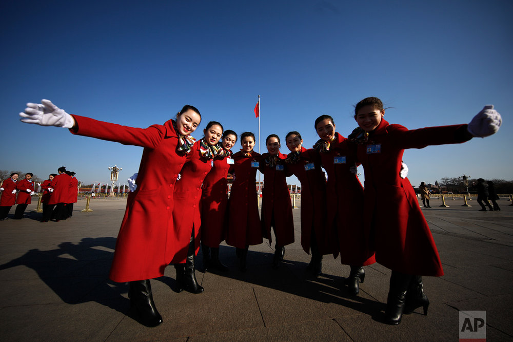 In this Sunday, March 5, 2017 photo, hospitality staff pose for photographs on Tiananmen Square during the National People's Congress held at the Great Hall of the People in Beijing. (AP Photo/Andy Wong)