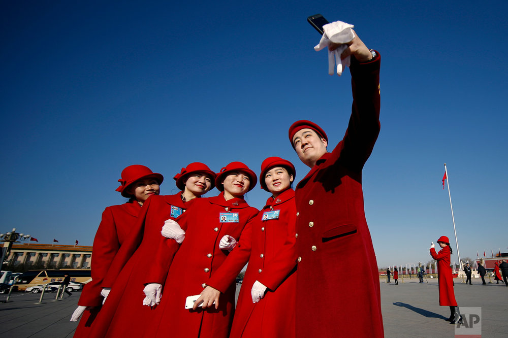 In this Sunday, March 5, 2017 photo, hospitality staff take selfies on Tiananmen Square during the National People's Congress held at the Great Hall of the People in Beijing. (AP Photo/Andy Wong)