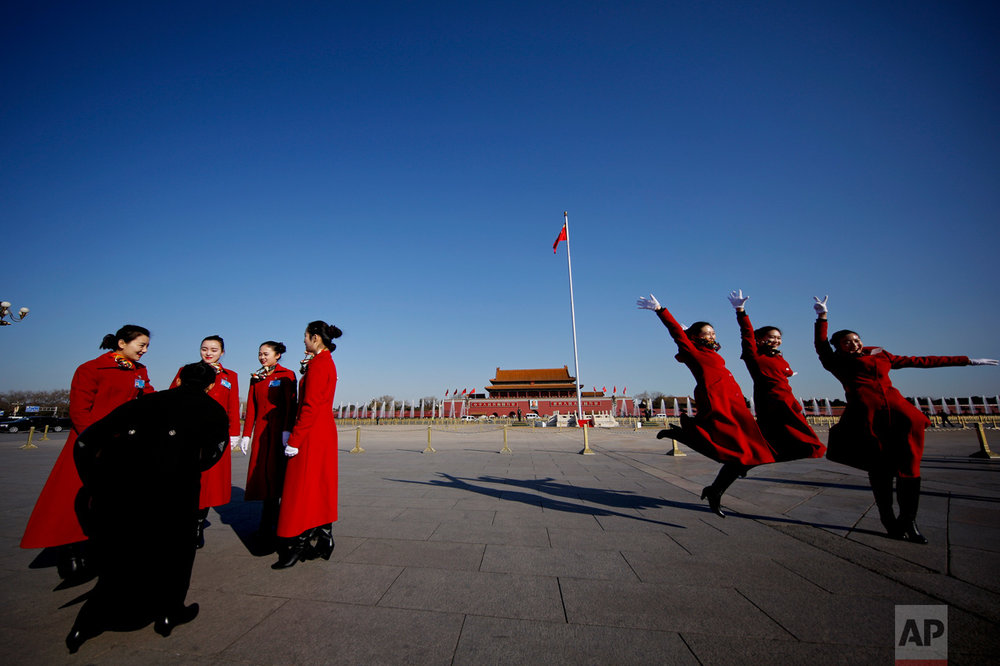 In this Sunday, March 5, 2017 photo, hospitality staff jump as they pose for photographs on Tiananmen Square during the National People's Congress held at the Great Hall of the People in Beijing. (AP Photo/Andy Wong)