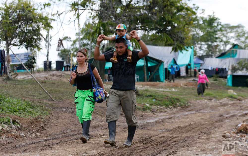 "In this Tuesday, Feb. 28, 2017 photo, FARC rebel couple Jerly Suarez, left, and Vicente Pulecio walk to a cooking class with their 9-month-old son Dainer at a rebel camp in a demobilization zone in La Carmelita, in Colombia's southwestern Putumayo state. ""It wasn't seen as viable for us to have children, because why is someone going to have them when there are bullets flying around?"" said Suarez, referring to the loosening of rules on baring children after the rebel group and the government reached an agreement to end their armed conflict. (AP Photo/Fernando Vergara)"